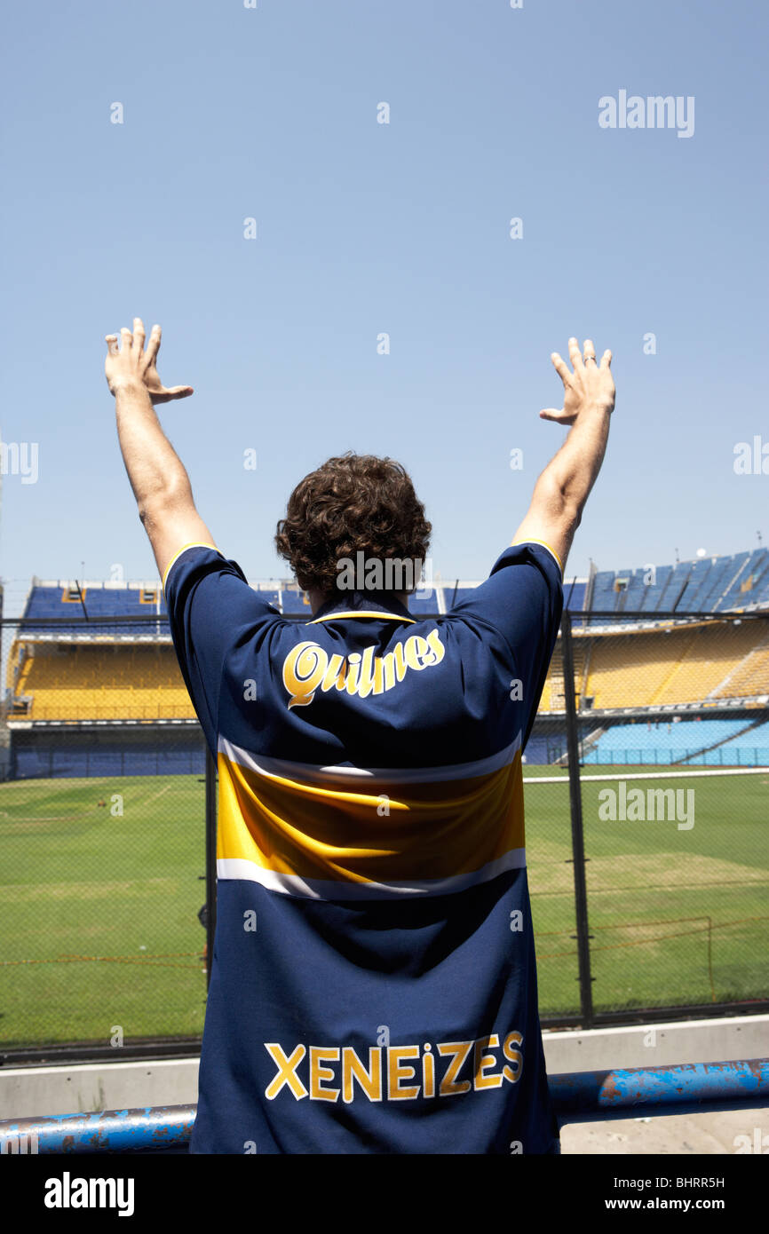 male boca juniors fan holds arms aloft in the interior of Alberto J Armando la bombonera stadium home to atletico - Stock Image