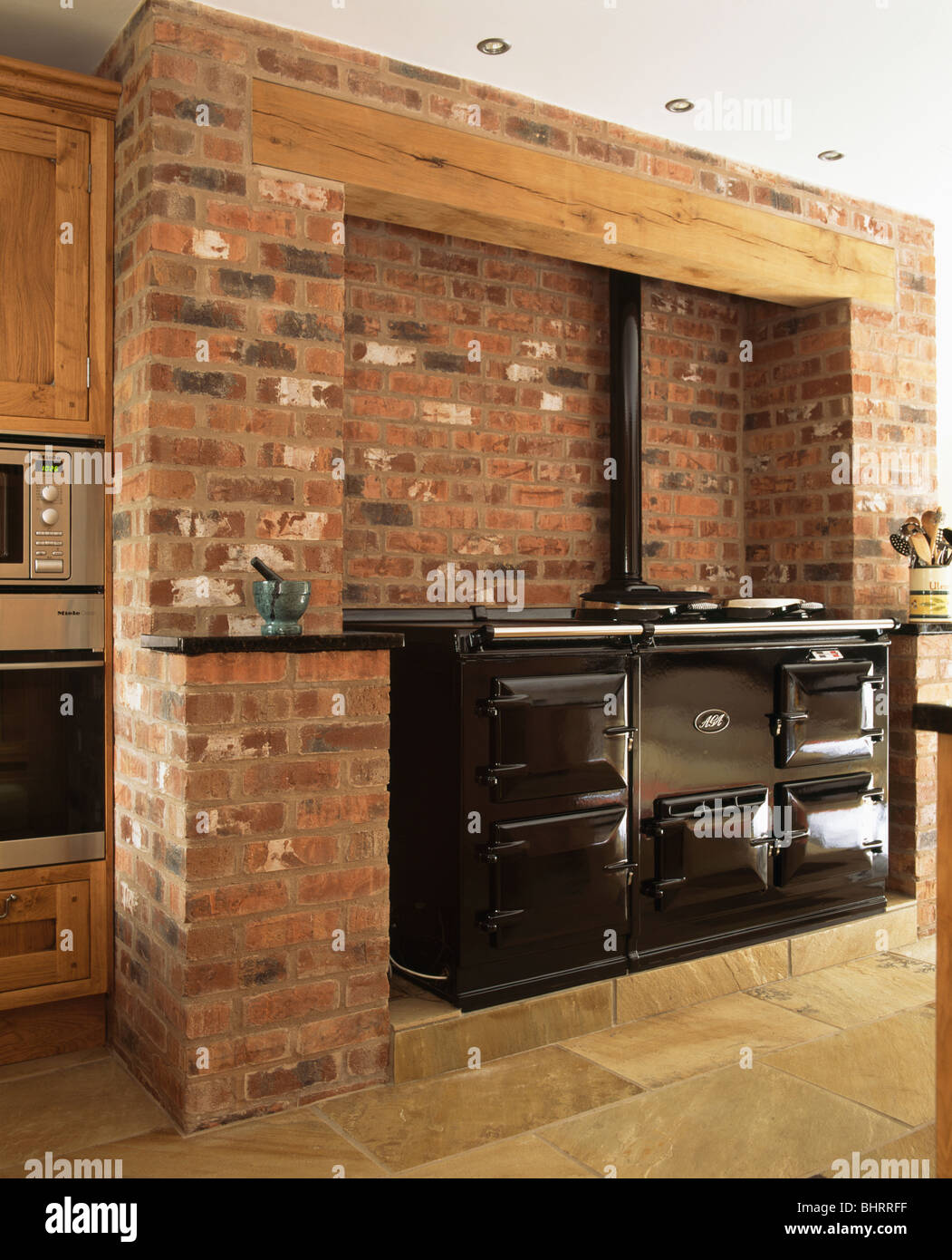 Black double Aga oven in exposed brick wall in country kitchen Stock