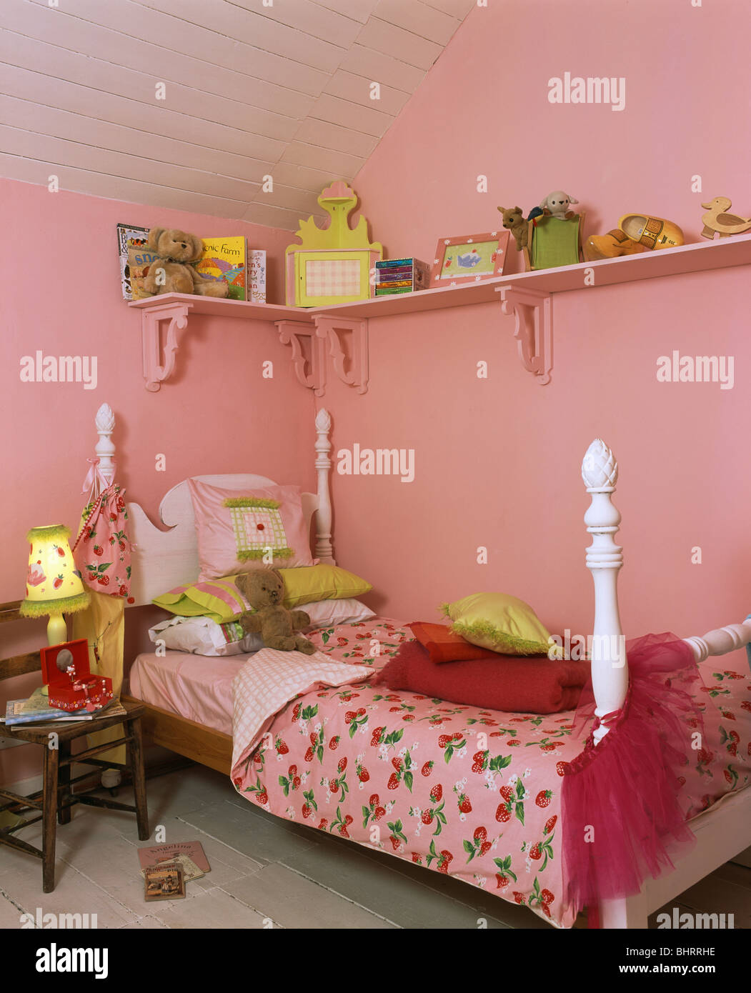 Toys On Pink Shelf Above Single Bed With Strawberry Print Bedlinen On Stock Photo Alamy