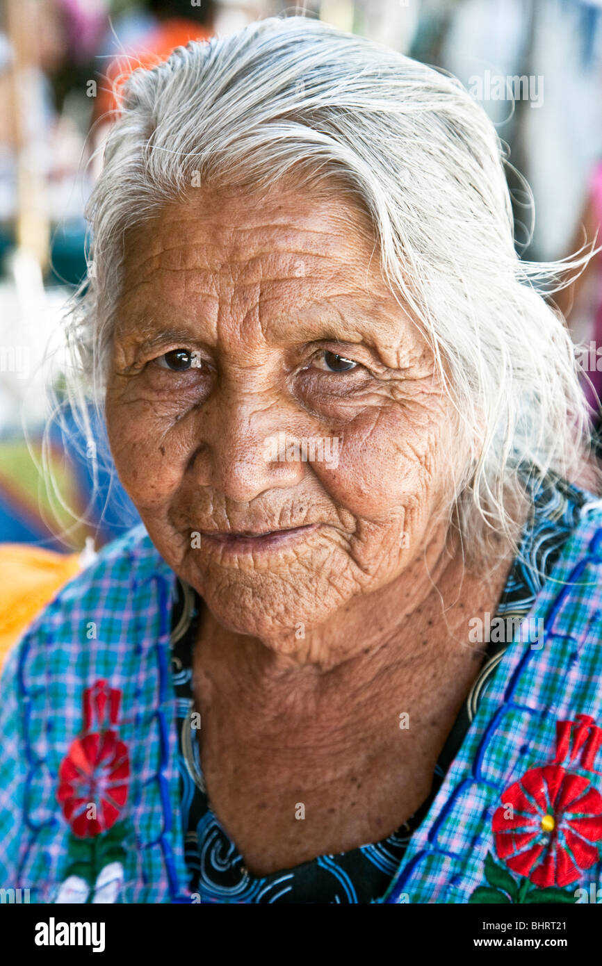 street portrait of vigorous wise old Mexican Zapotec indian woman peddler wearing embroidered apron in Oaxaca City - Stock Image