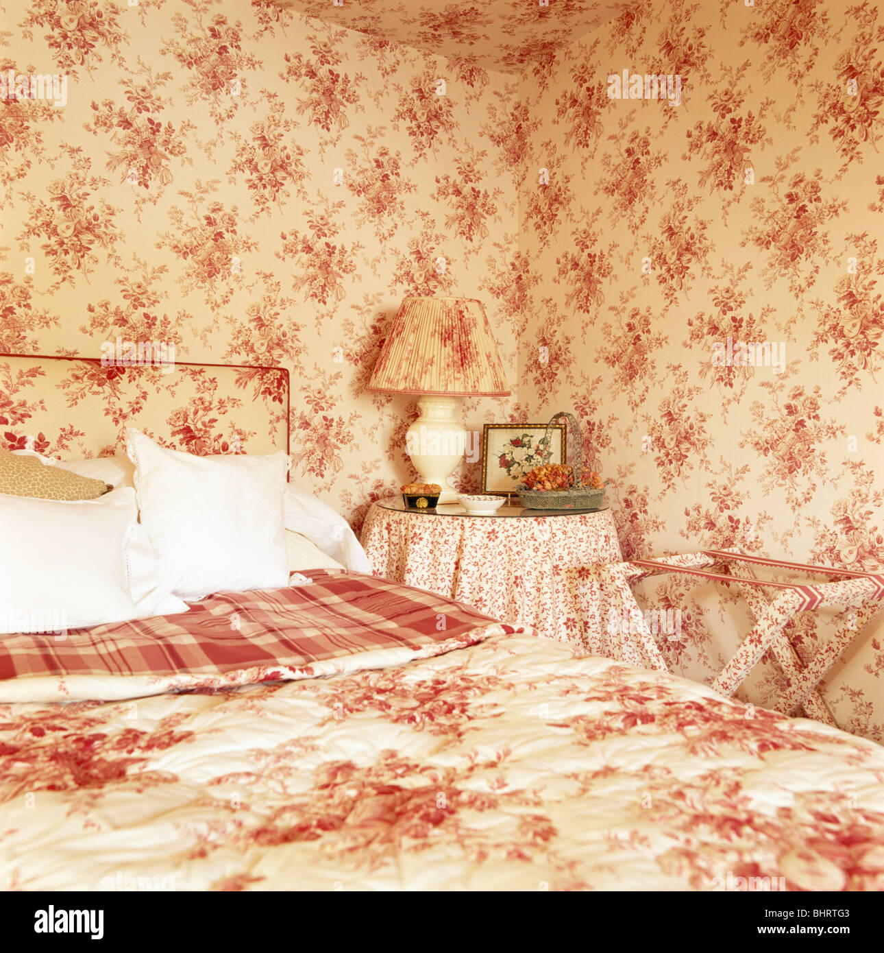 Pink Floral Wallpaper And Matching Quilt In Country Bedroom Stock