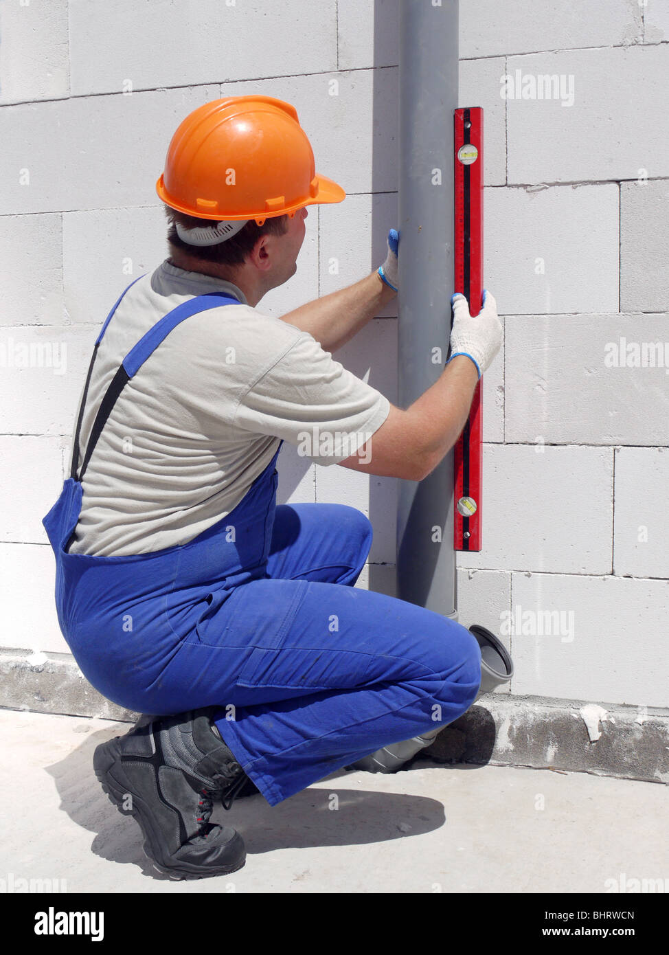 Plumber using level for checking plumb line of assembled pvc sewage pipes inside unfinished house - Stock Image