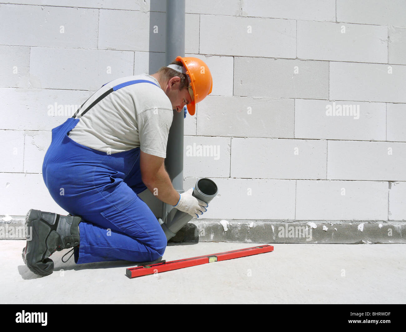 Plumber fitting pvc sewage pipes inside newly built house - Stock Image