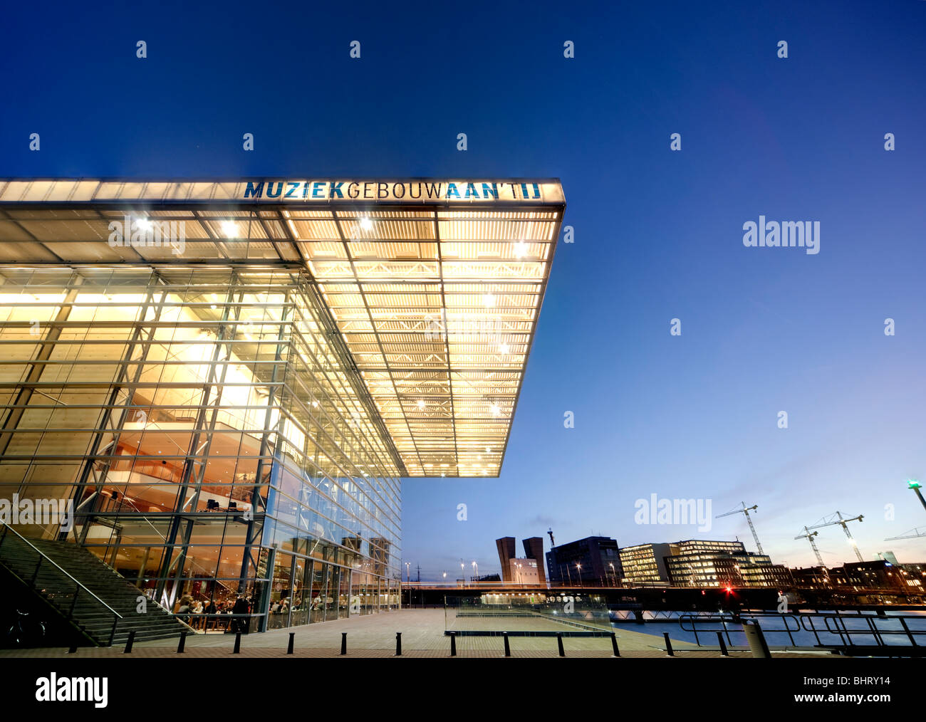 Amsterdam Muziekgebouw aan 't IJ, Music Building at the IJ, and the Star Ferry Restaurant at dusk. - Stock Image