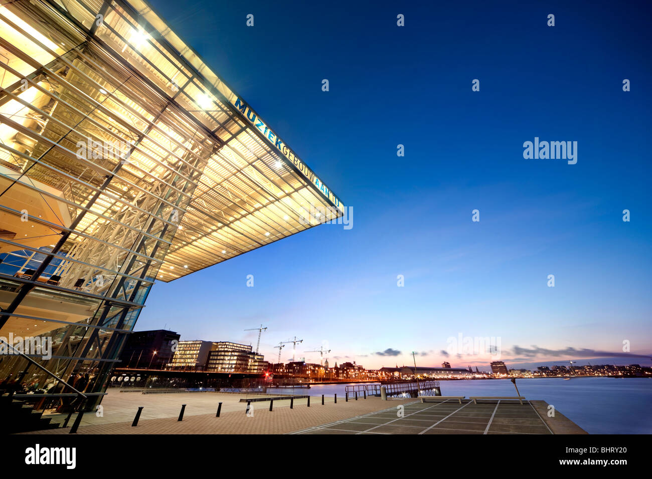 Amsterdam Music Building at the IJ and the Star Ferry Restaurant at dusk with views towards the Central Station - Stock Image