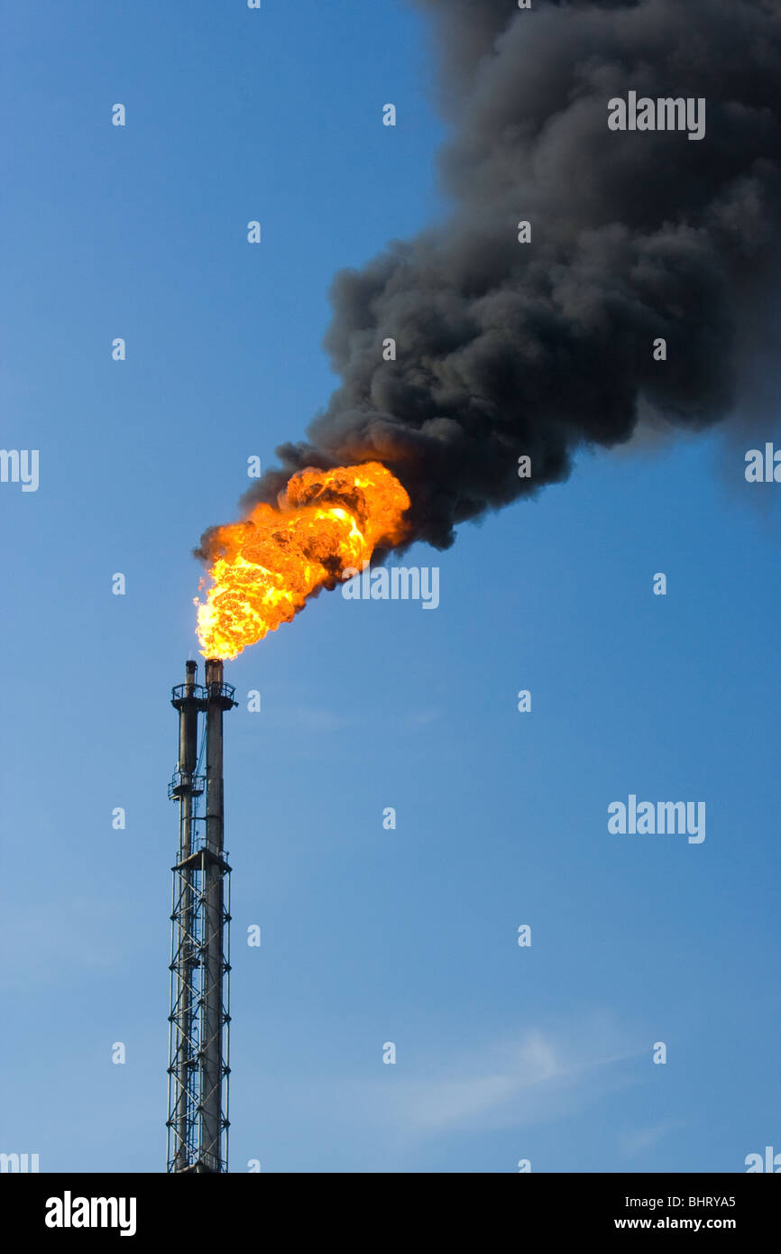Factory funnel burning with large flame and throwing thick cloud of smoke - Stock Image