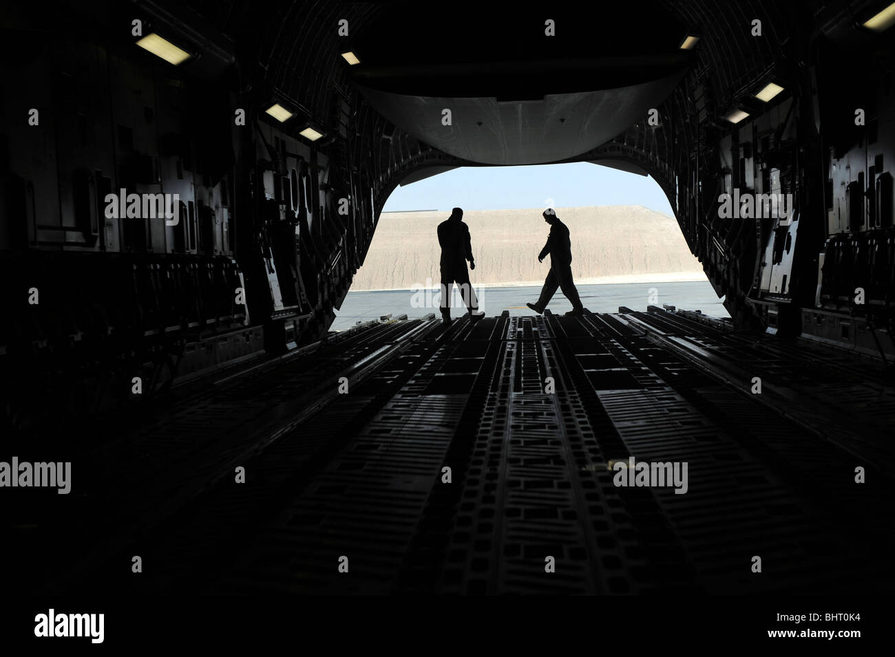 C-17A Globemaster III loadmasters go through prefight checks on the ramp. - Stock Image