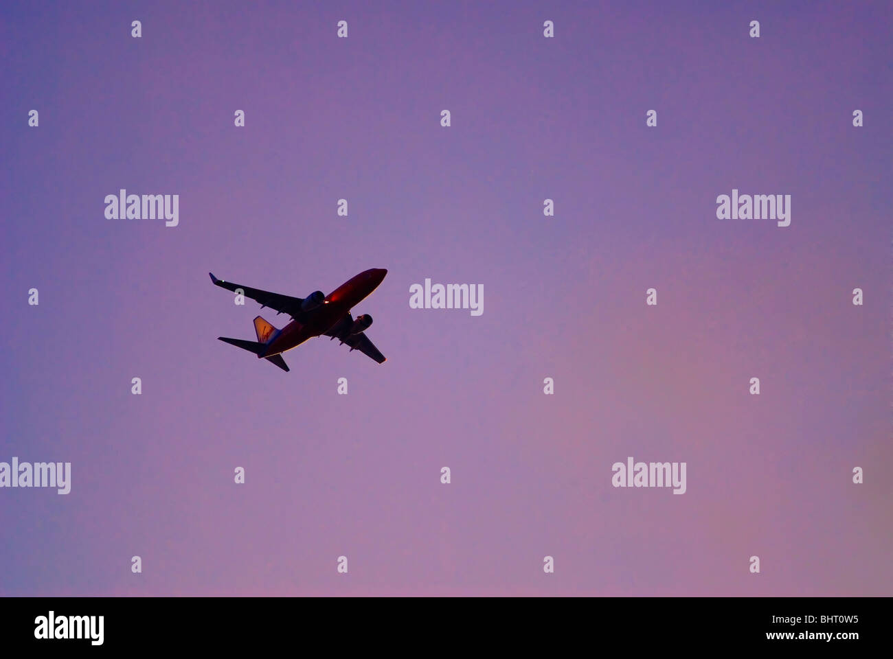 Airliner flying in sunset sky - Stock Image
