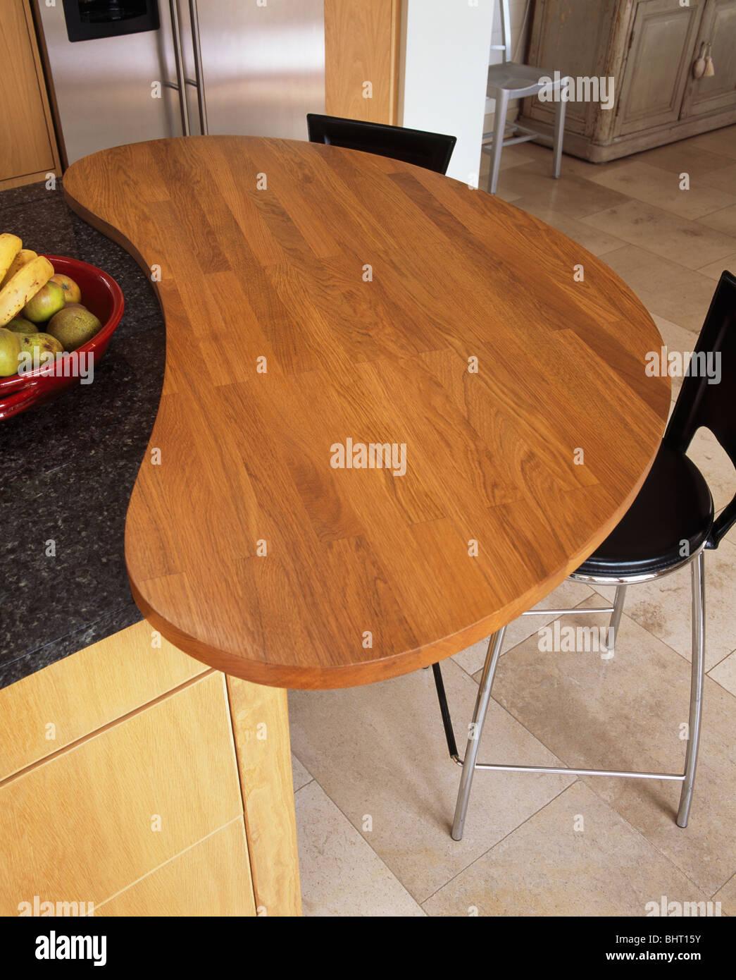 Curved Wood Breakfast Bar On Island Unit In Modern Kitchen