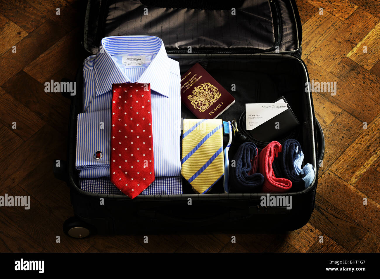 A suitcase containing travel items for a man - Stock Image