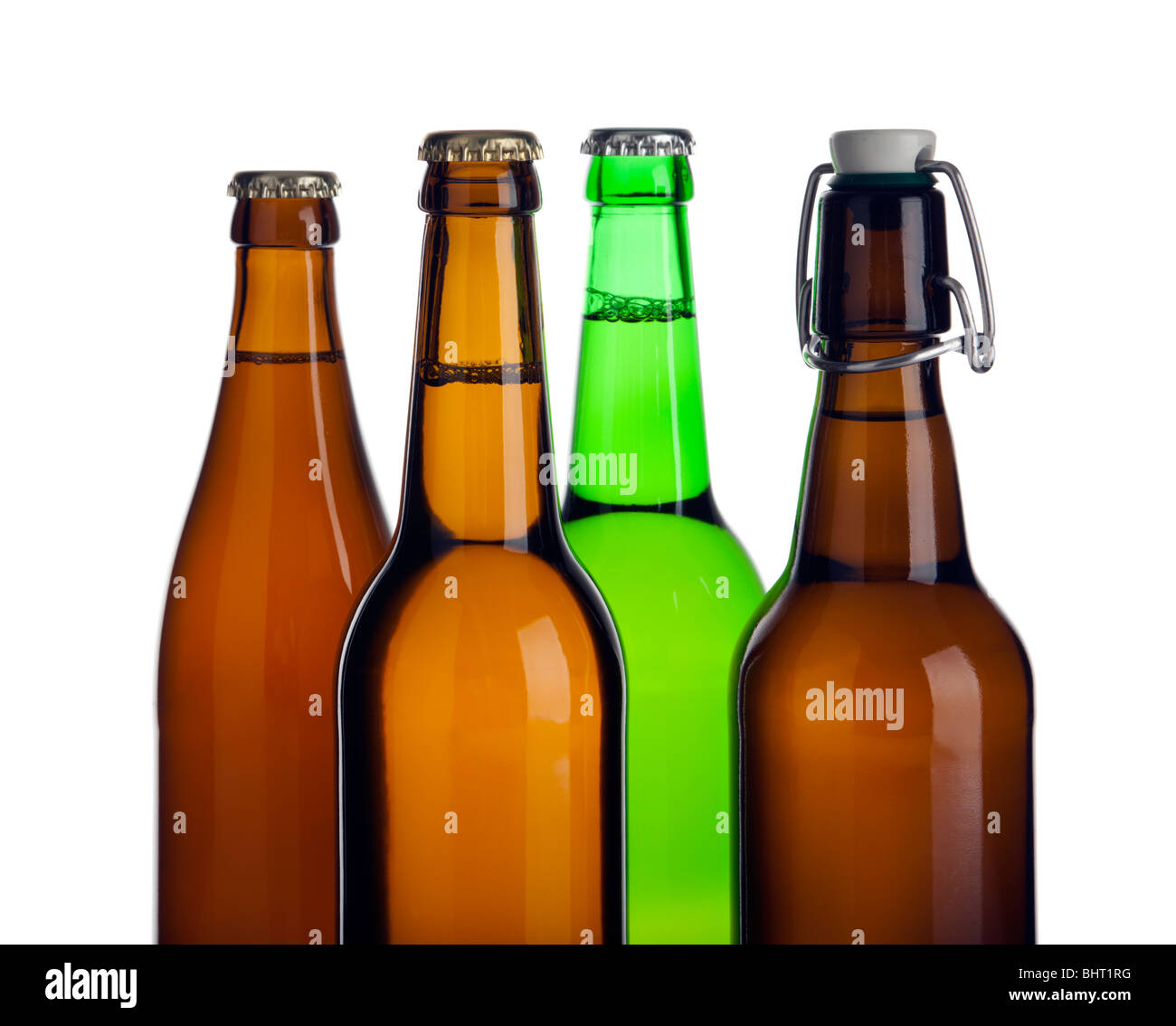tops of four different beer bottles without labels, cutout - Stock Image
