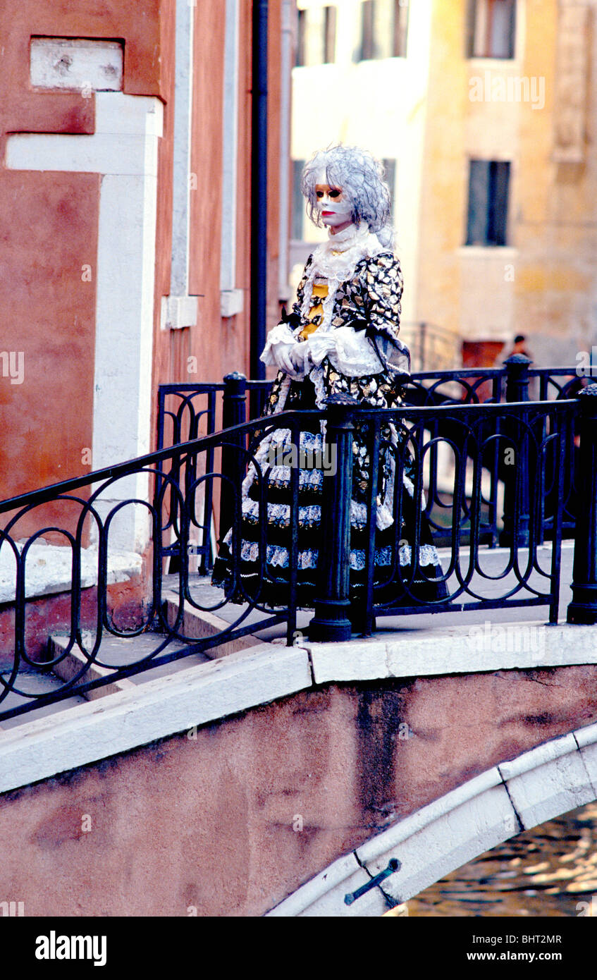 Lady in costume crossing over a small bridge in Venice during the Carnival - Stock Image
