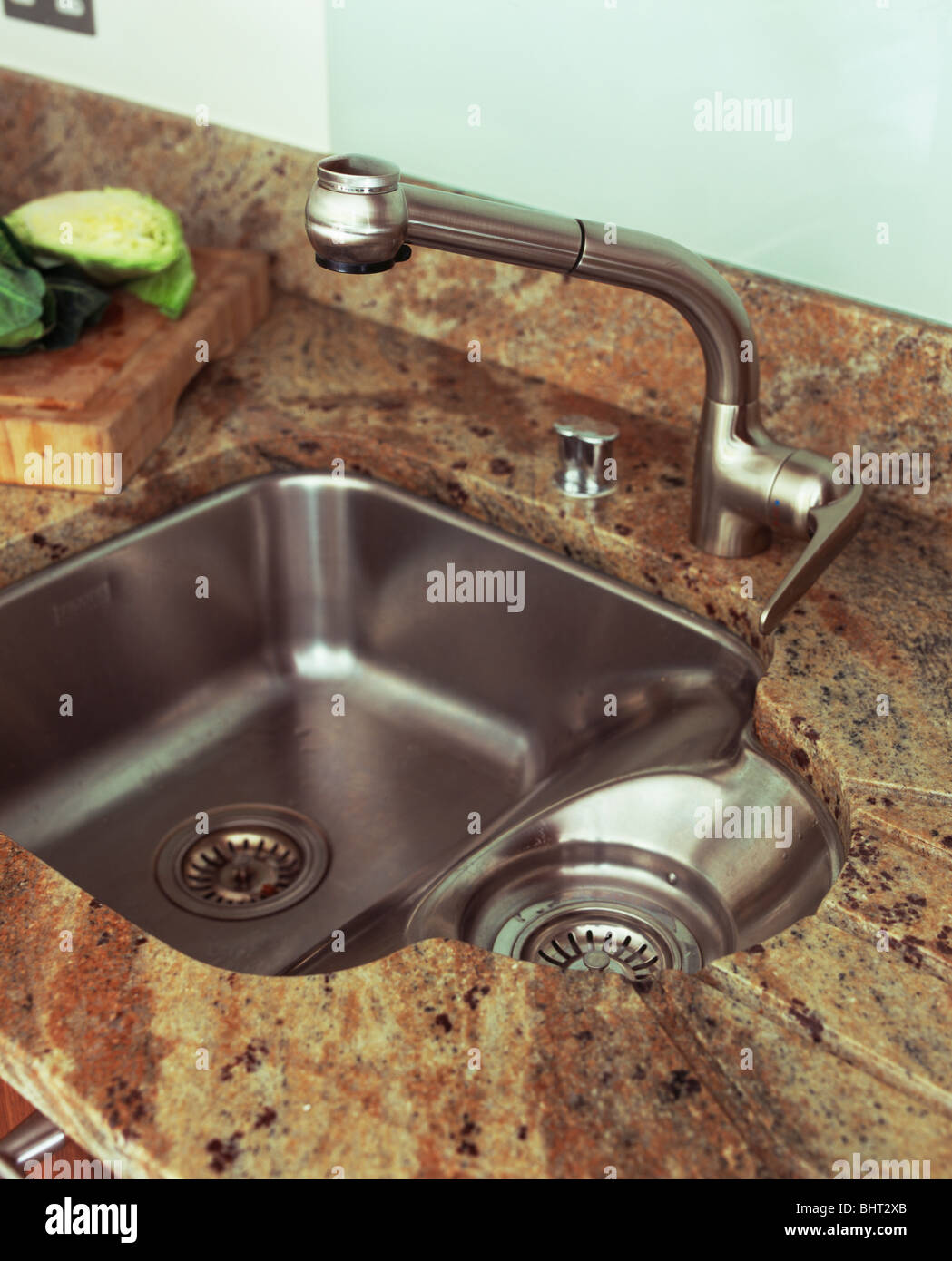 Close Up Of Stainless Steel Tap And Sink With Integral Drainer In Brown  Granite Worktop