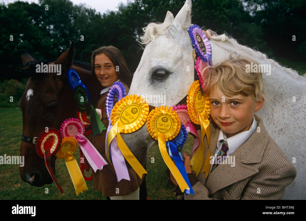 Two young girls stand with their beloved rosette-winning ponies at a gymkhana in Cheltenham, Gloucestershire. - Stock Image