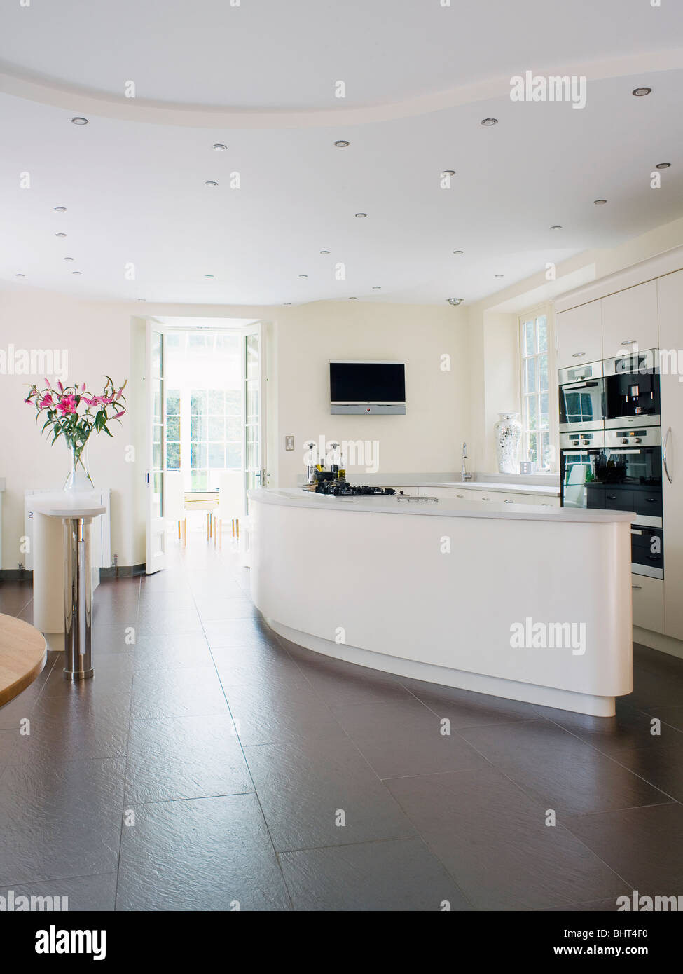 Slate flooring in large modern white kitchen with curved island unit ...