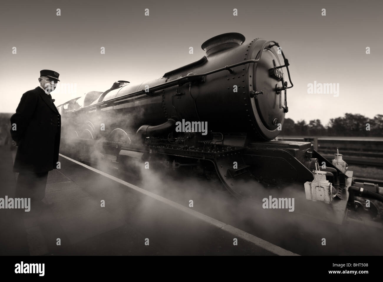 Preserved Steam locomotive and train guard awaiting departure time at a railway station in monotone. - Stock Image
