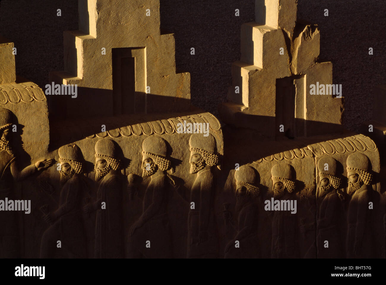 Relief sculpture of the subject people of the Achaemenian Empire climb the stairway Persepolis, Iran - Stock Image
