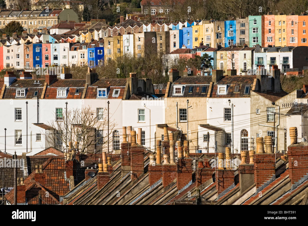 Old terraced housing tightly packed on a hill in sunlight - Stock Image