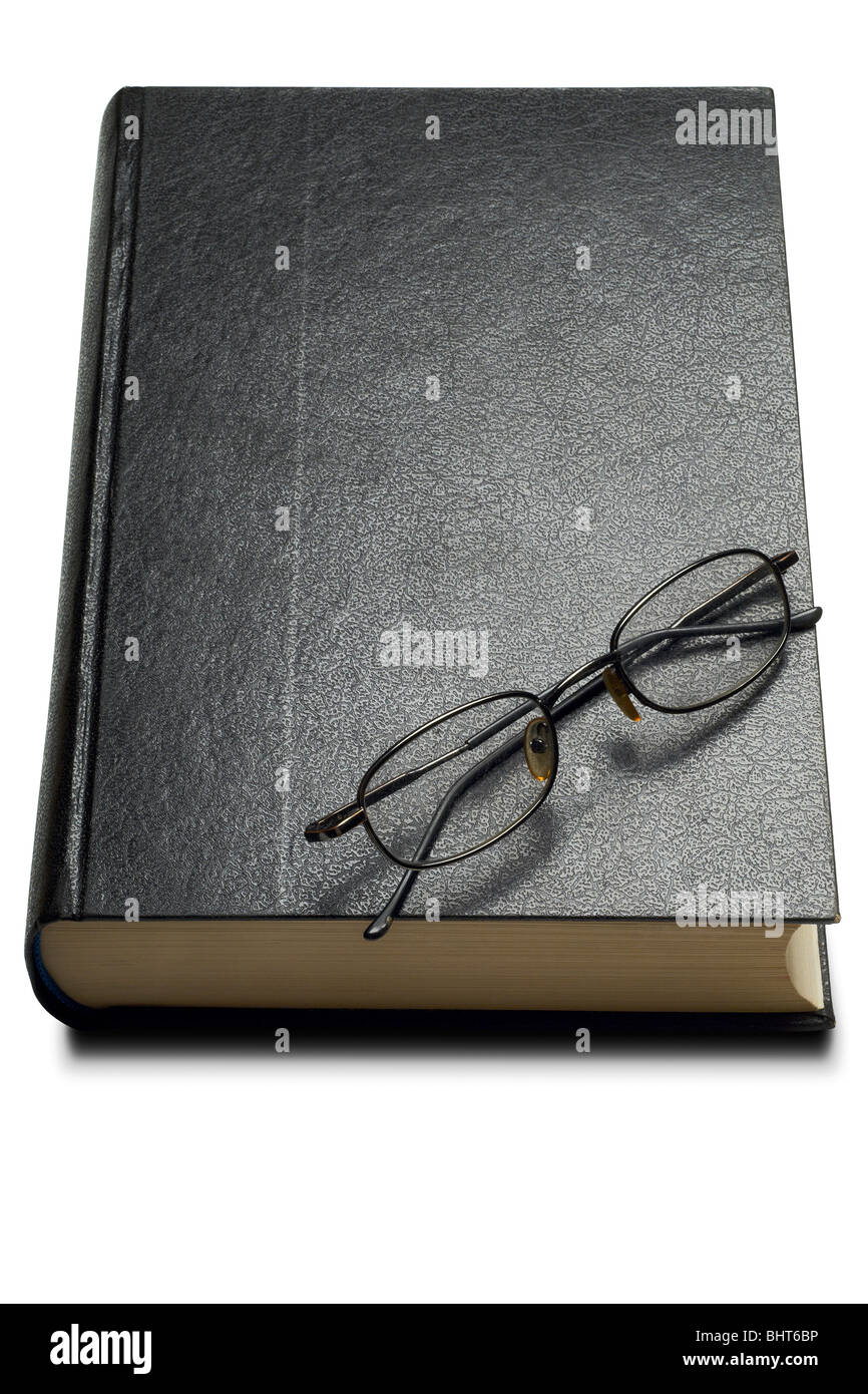 a hardcover book with reading glasses on - clipping path - Stock Image