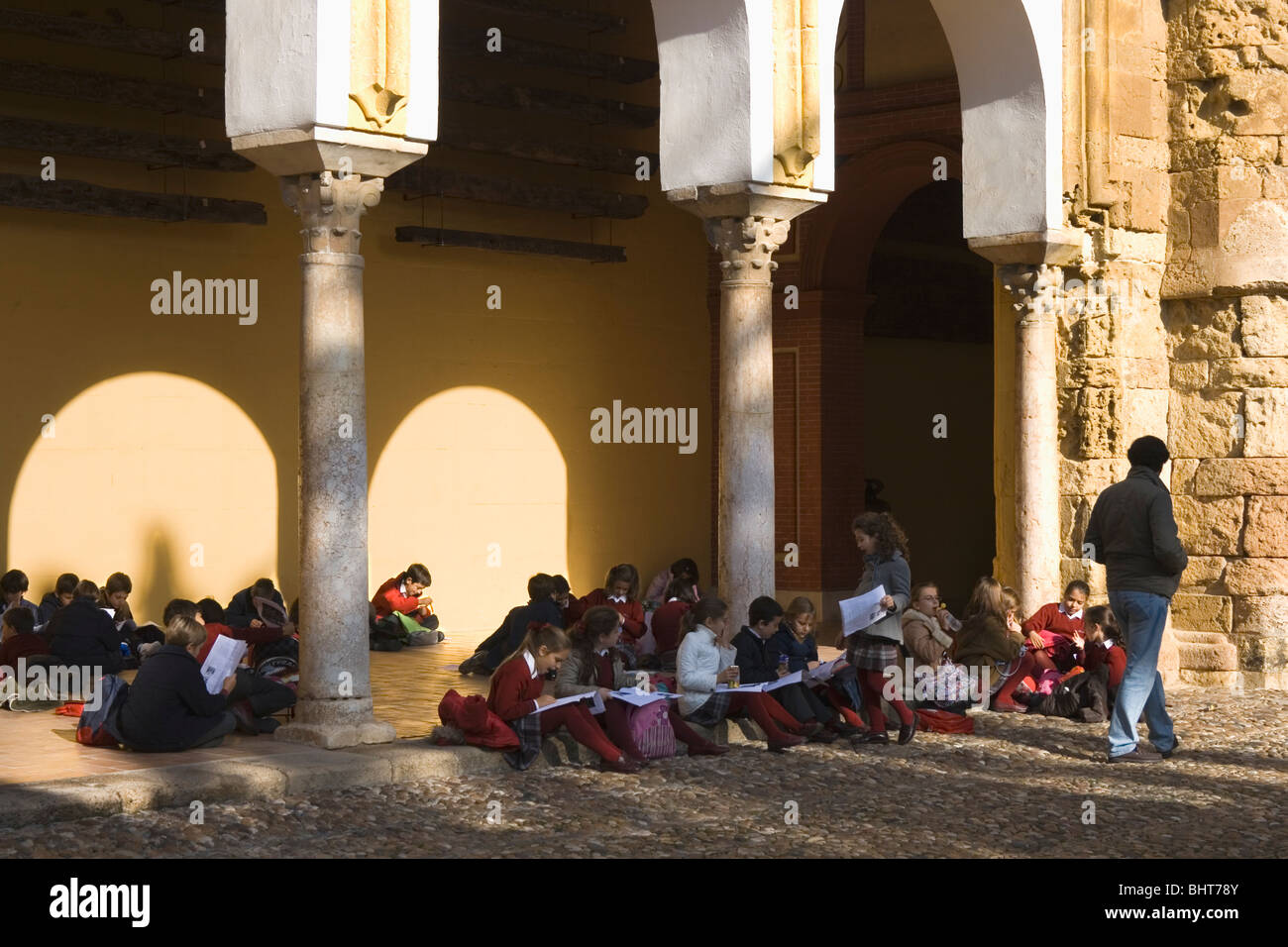 Spanish schoolchildren in the patio of The Great Mosque, Cordoba, Spain studying its history. - Stock Image