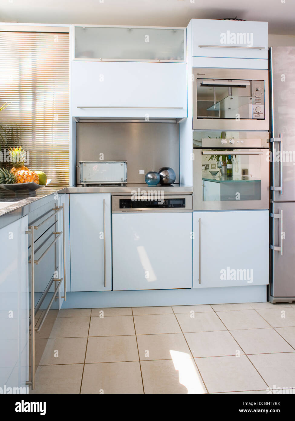 Stainless steel double oven and fitted dishwasher in modern white stainless steel double oven and fitted dishwasher in modern white kitchen with cream ceramic floor tiles dailygadgetfo Image collections