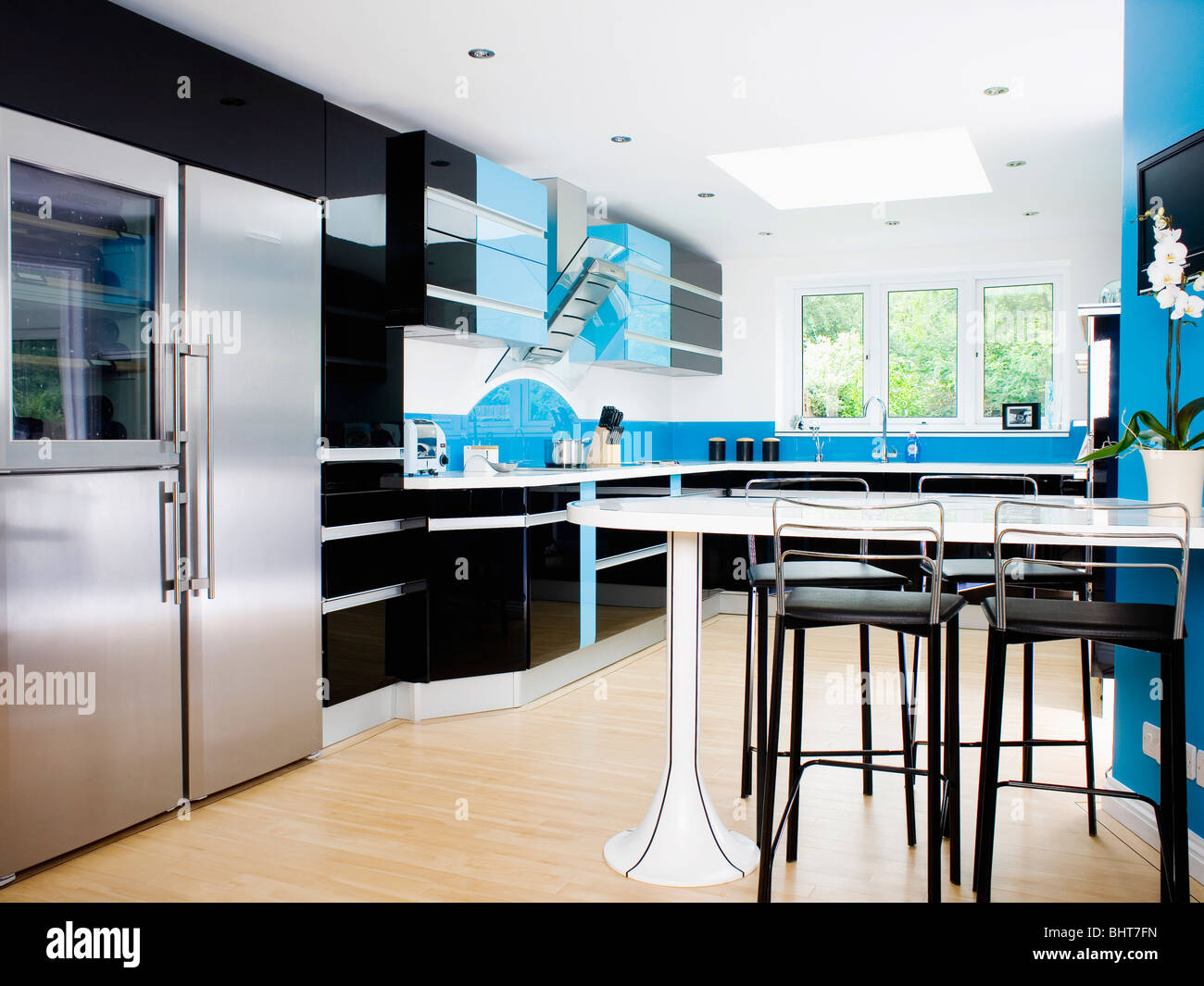 Black Stools At Fitted White Table In Blue And Black Modern Kitchen With  Large Stainless Steel American Style Fridge Freezer