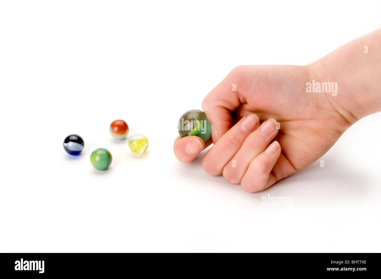 hand on white with marbles - Stock Image