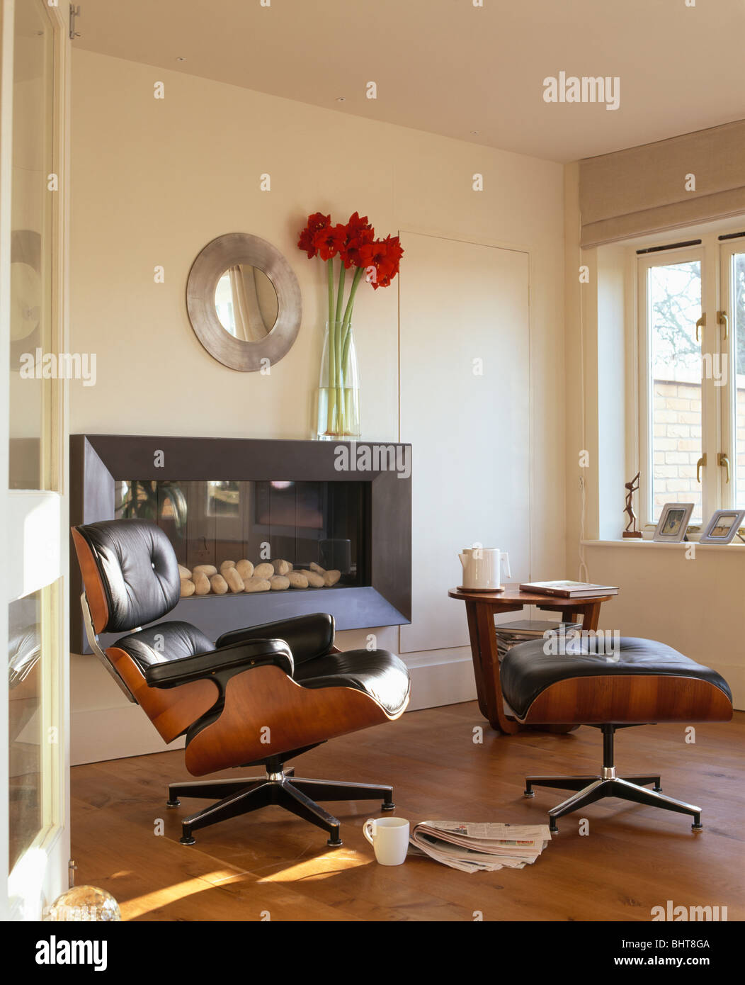black leather charles eames armchair and stool in front of modern