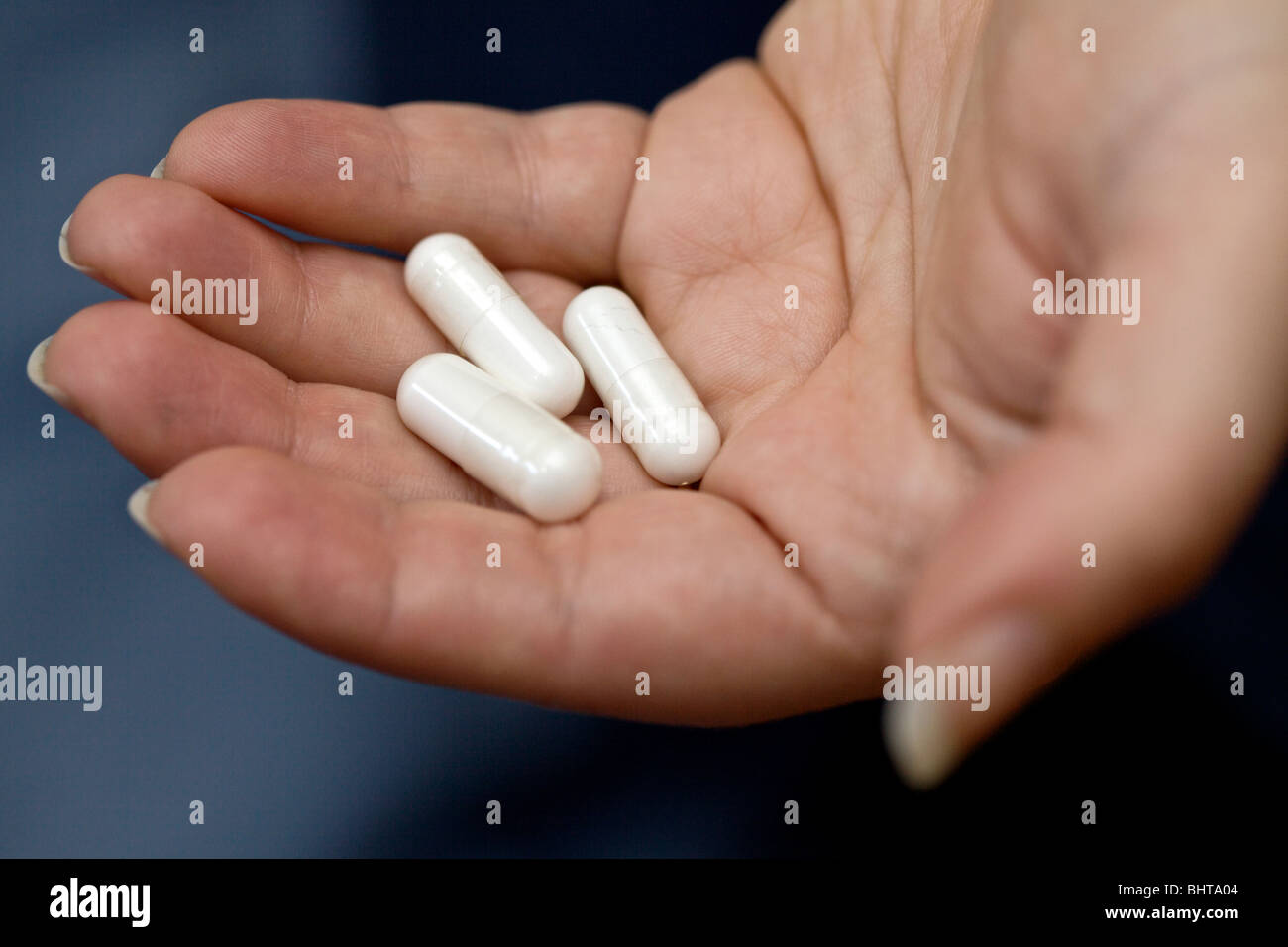 Capsules containing white powder in woman's hand. - Stock Image