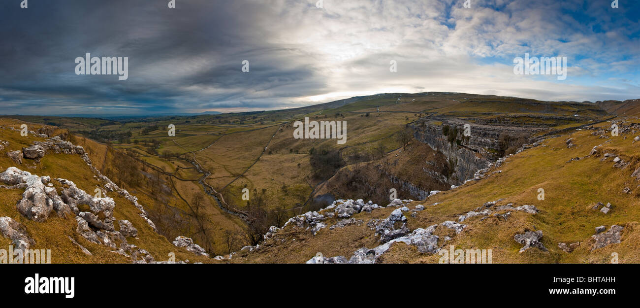 A panorama of malham cove and the surrounding area. The huge cliff face was formed by glacial meltwater eroding - Stock Image