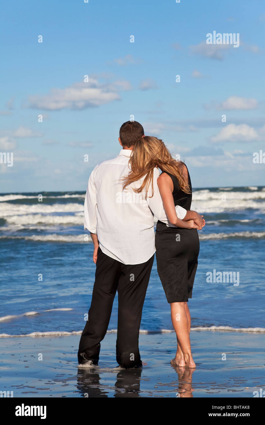 A young man and woman romantic couple in love arms around each other cuddling on a beach with a bright blue sky - Stock Image