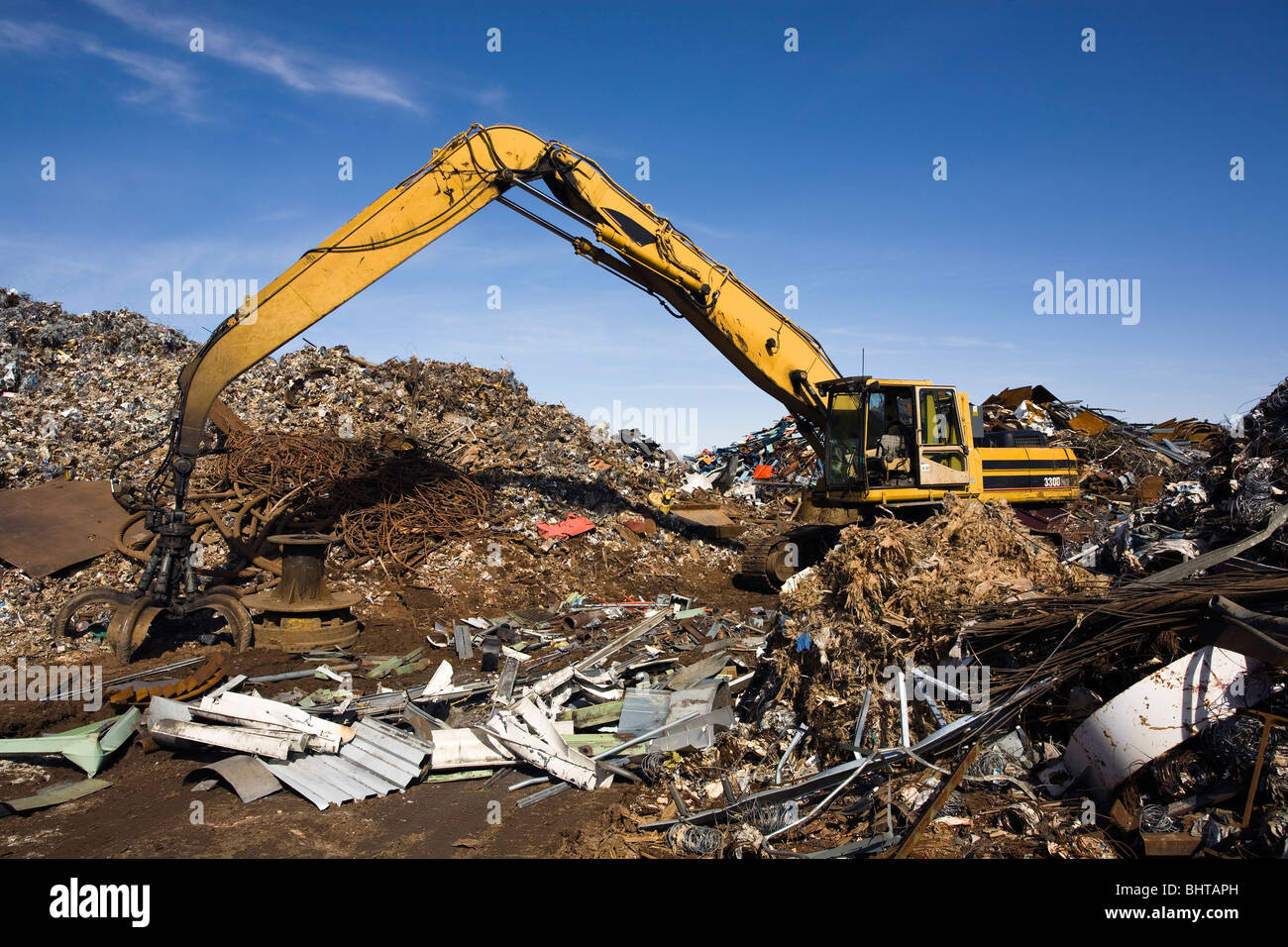 Excavating machine, with large grapple claw, at scrap metal yard. - Stock Image