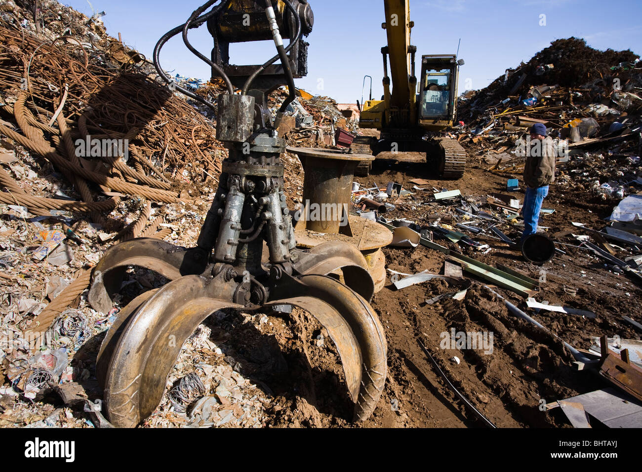 Excavating machine, with large grapple claw, at scrap metal yard. Man in the scene. - Stock Image