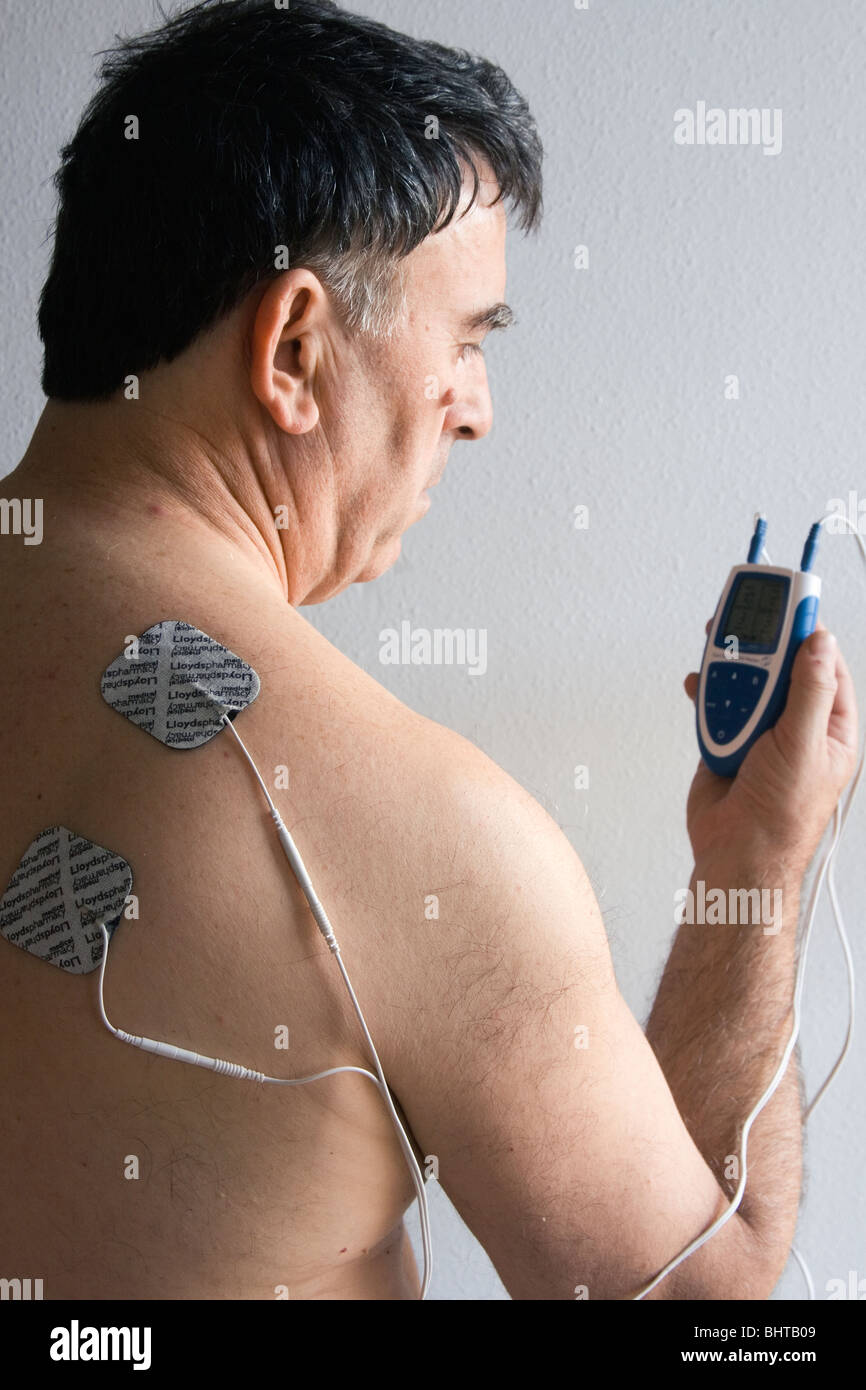 Man using a Dual Channel TENS Machine for pain relief. - Stock Image