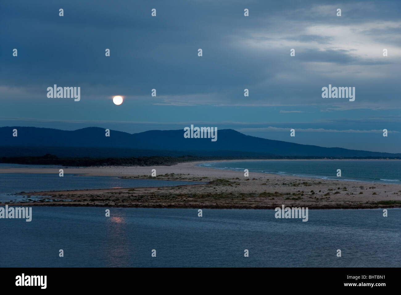 Full moon rising at dusk over mountains, lake, and sea. Location: Mallacoota, East Gippsland, Victoria, Australia Stock Photo