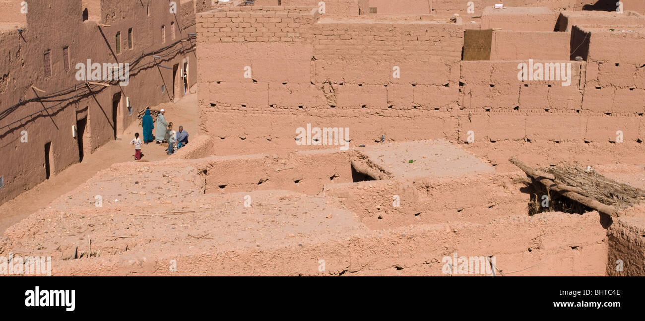 A family walking through the mud brick and adobe buildings of Mhamid el Ghizlane in Southern Morocco - Stock Image