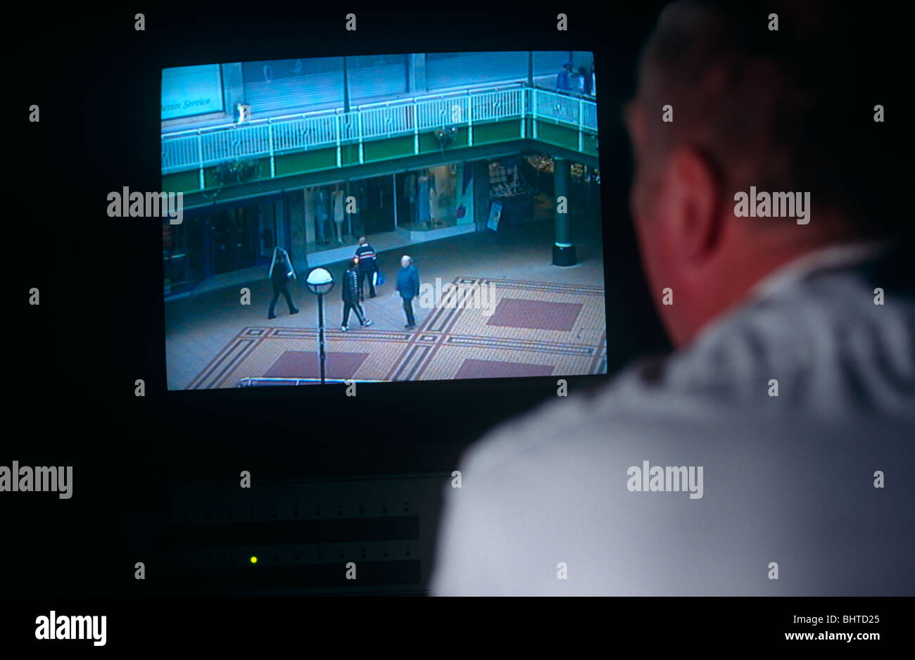 From the darkened room of Coventry council's CCTV control room a council camera operator spies on innocent pedestrians. - Stock Image