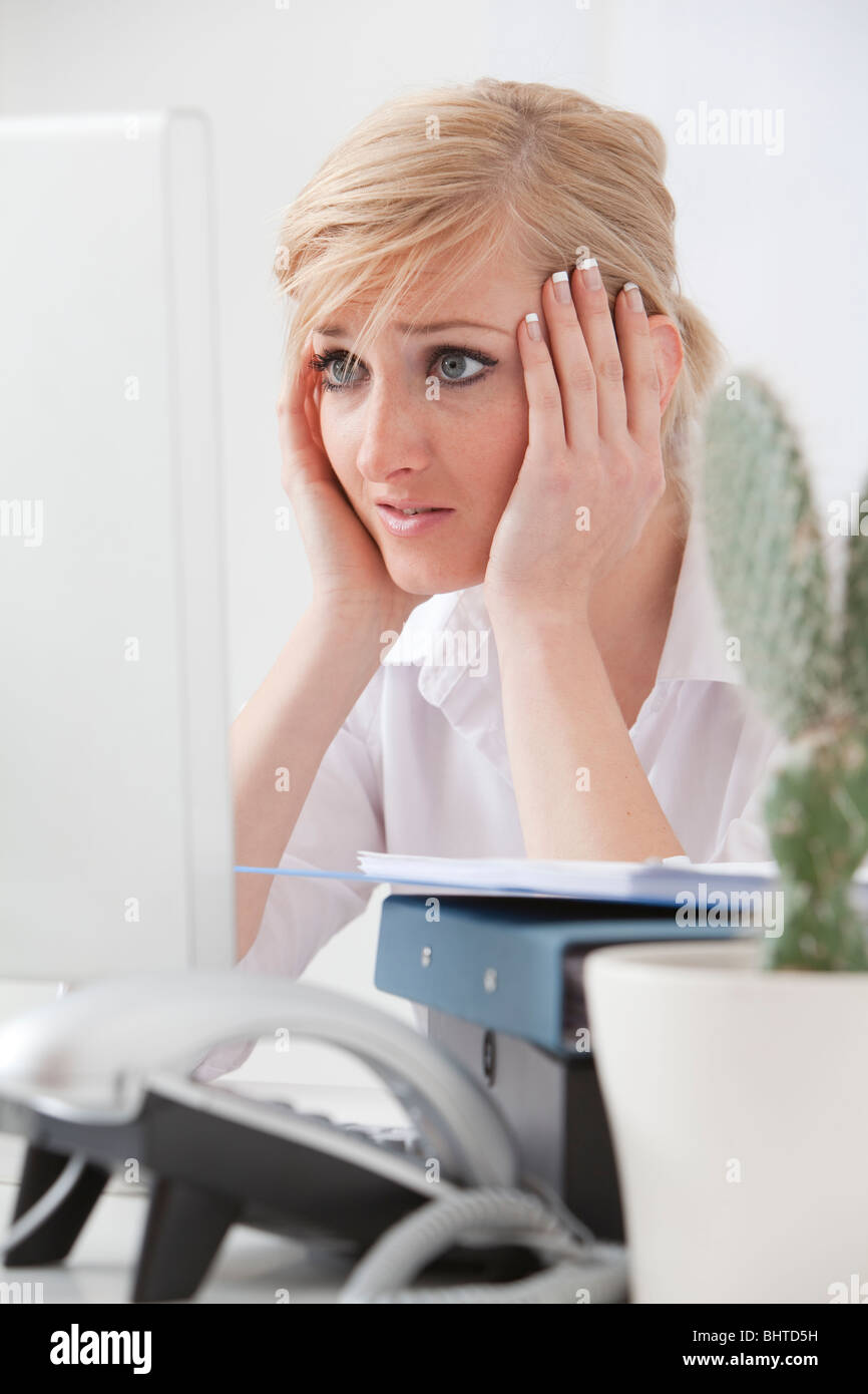 tired stressed Young business woman looking at bad news on her desk computer - Stock Image