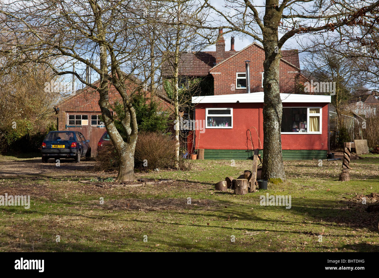Country cottage with a mobile home in the garden, Hampshire, England. - Stock Image