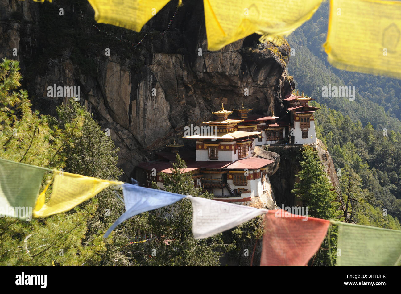 temple on a cliff face with prayerflags - Stock Image