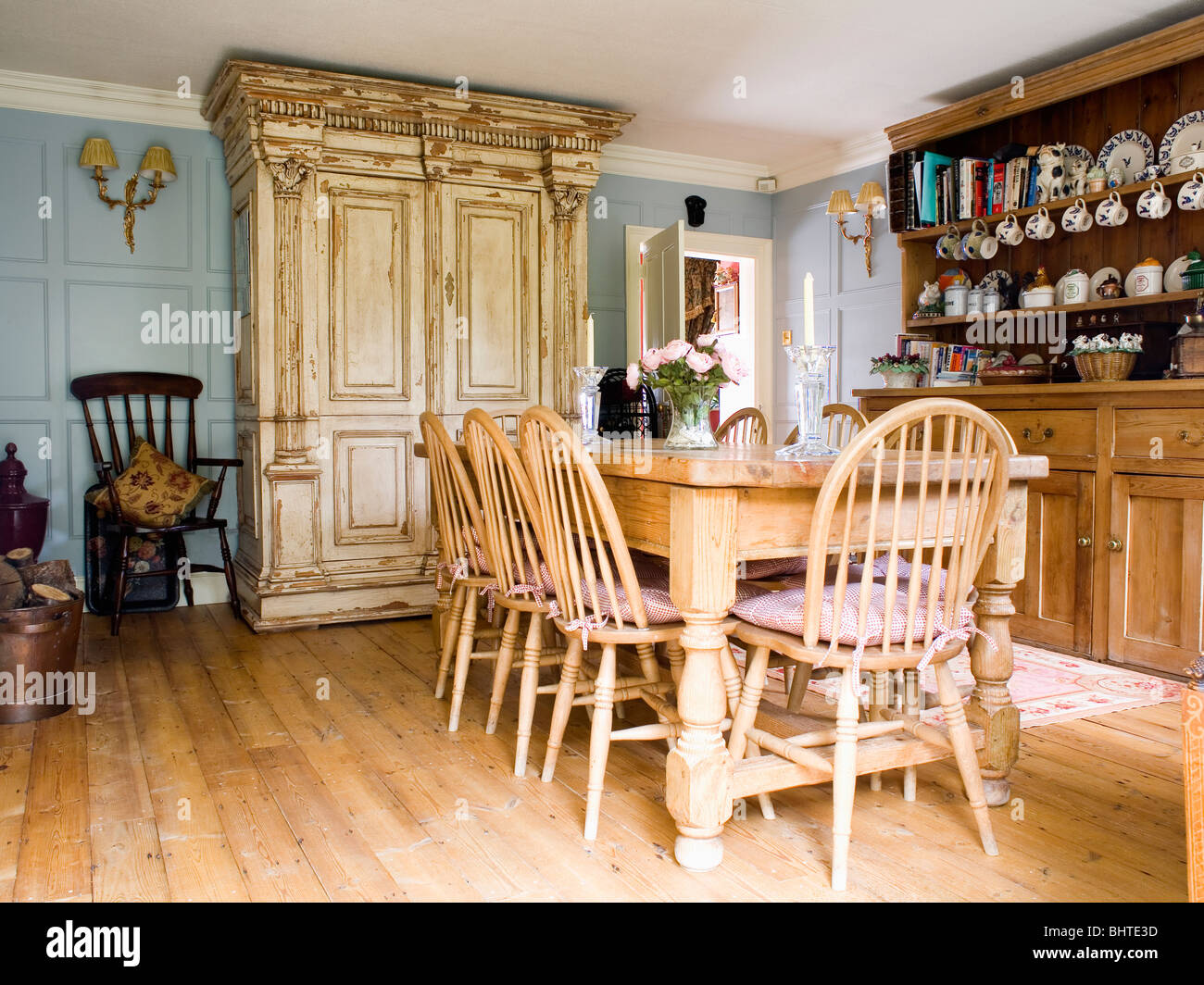 https://c8.alamy.com/comp/BHTE3D/wheel-back-chairs-and-pine-table-in-country-dining-room-with-large-BHTE3D.jpg