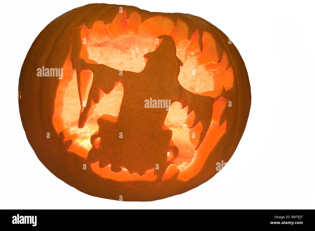 Scary Halloween pumpkin lantern with carved witch shape and illuminated with a candle glowing inside - Stock Image