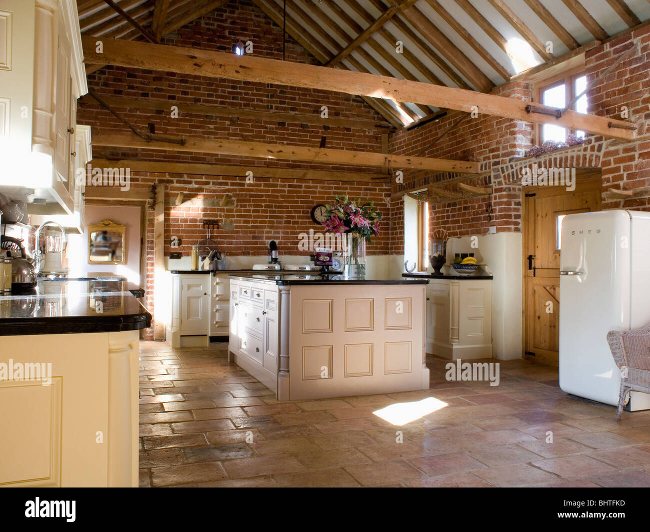 Stone Flagged Floor And Island Unit In Large Barn Conversion Kitchen With  Beamed Apex Ceiling