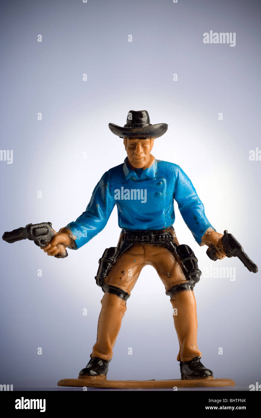miniature toy cowboy drawing both pistols - Stock Image