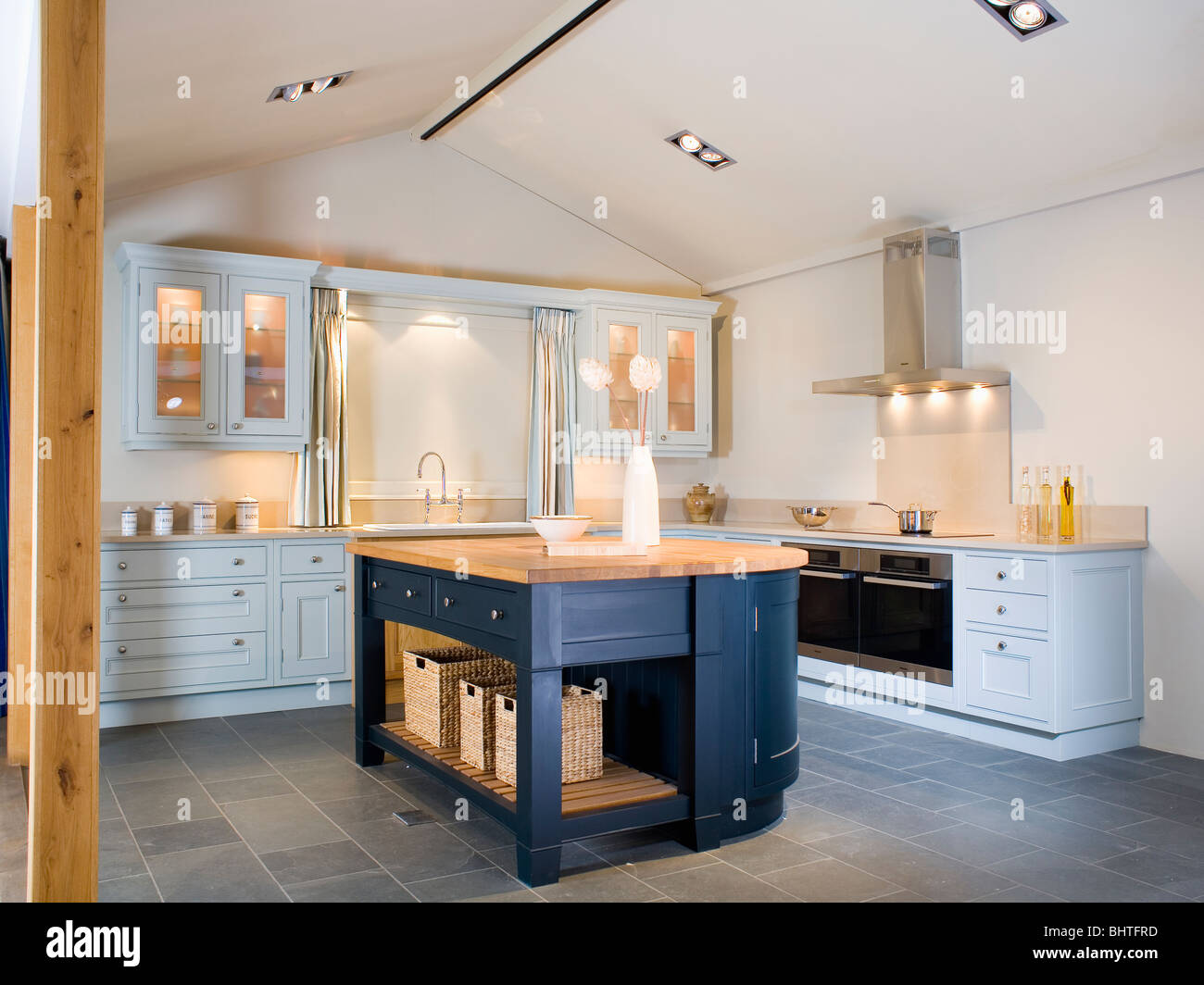 Dark Blue Island Unit And Slate Flooring In Modern Kitchen With Pale Blue  Fitted Units