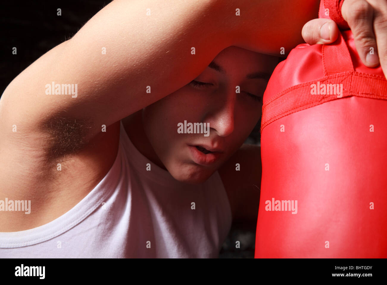 Tired sportsman resting on punch bag to recover from training exercise - Stock Image