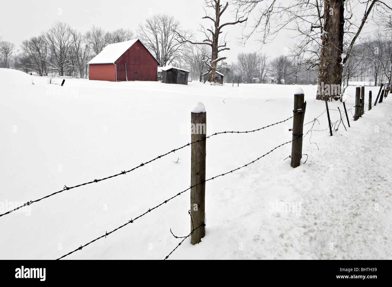 Red Barn and Fence in the Snow in Floyd County, Indiana - Stock Image