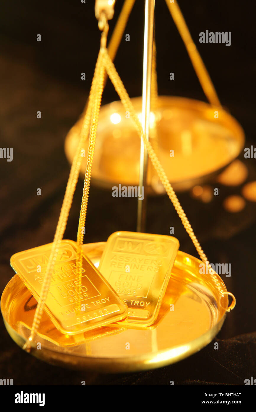 One ounce gold bars in tray of balance scale - Stock Image