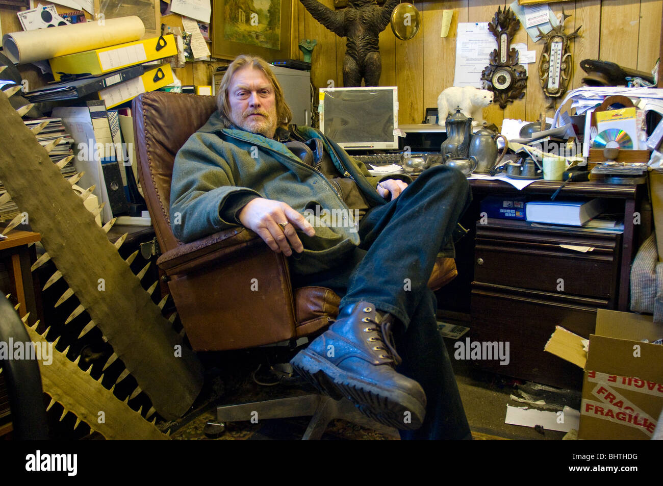 Antique Dealer, surrounded by collectibles in his office - Stock Image