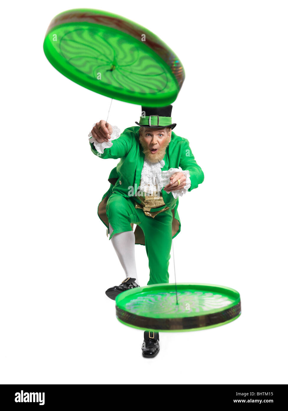 Cheerful Leprechaun playing with two flip n flyers isolated on white background - Stock Image